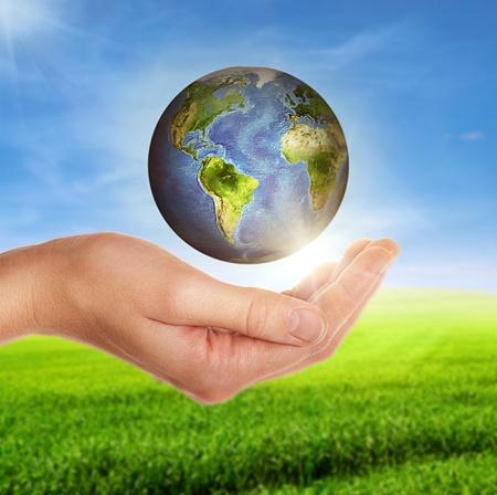 weibliche Hand hält Globus über der grünen Wiese und bewölkten blauen Himmel