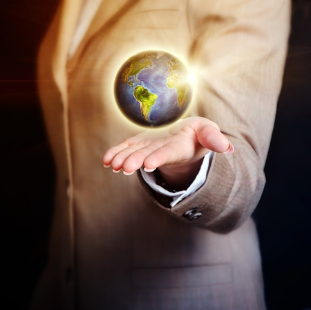 sea world: business woman holding earth globe in her hand over black background