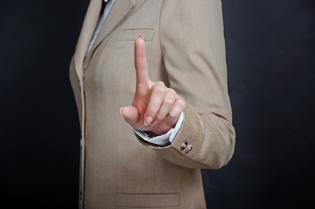 female hand in suit reaching or touching something with fingers over black Stock Photo - 13251231