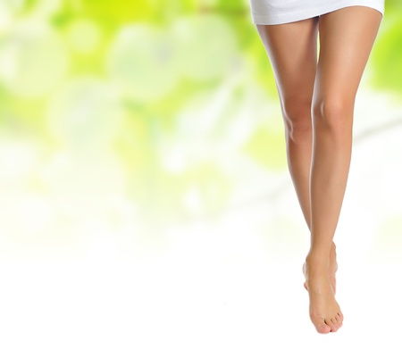 sexy naked slender female legs making step over green natural background Stock Photo - 13423491
