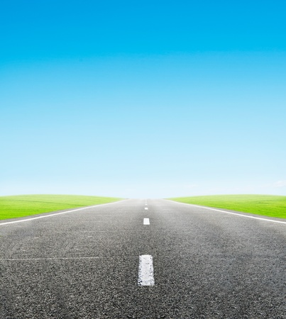green field and road over blue sky - travel and tranportation concept Stock Photo