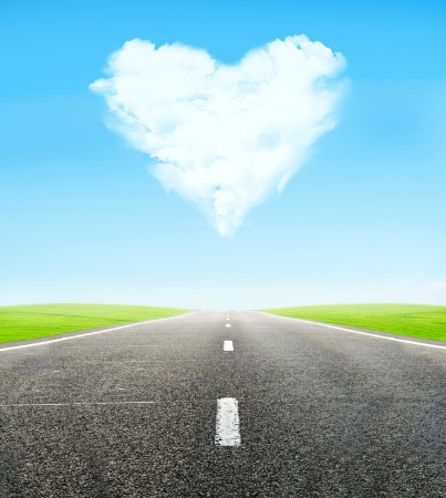 green field and road over blue sky with clouds in shape of  heart - honeymoon travel concept Stock Photo