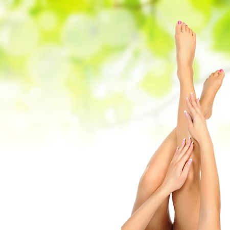 spa pedicure: healthy sexy slender female legs being massaged over green natural spring background - spa and healthcare concept