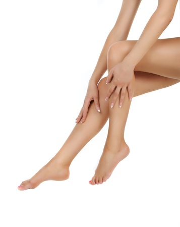 female legs over white being massaged with hands - heathcare and hygiene concept