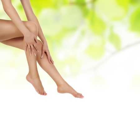 massaged:  female legs over green natural background being massaged with hands - heathcare and hygiene concept Stock Photo
