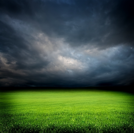 stormy dramatic sky and green field of grass at night photo