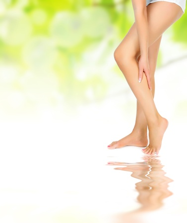 female legs being massaged with hands over green reflected in water waves