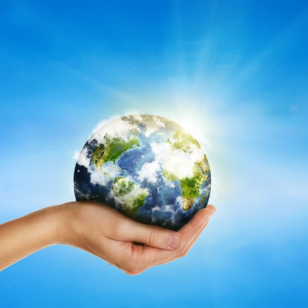 female hand holding globe over blue sky - environment protection and travel concept -Elements of this image furnished by NASA Stock Photo