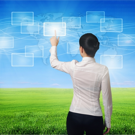 business woman pushing virtual icons in interface over green grass and blue sky landscape photo