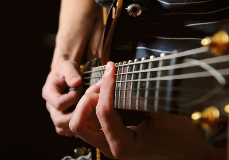 roll up: close up shot of strings and guitarist hands playing guitar over black - shallow DOF with focus on hands Stock Photo