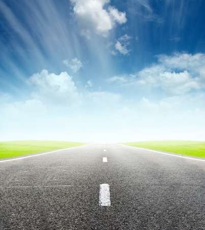 move ahead: green field and road over blue cloudy sky - travel and tranportation concept