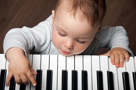keyboard keys: portrait of little baby child  play music on black and white piano keyboard Stock Photo