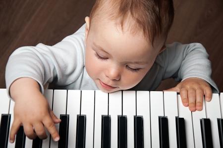 tocando el piano: Retrato del pequeño bebé música juego de niños en el teclado del piano blanco y negro