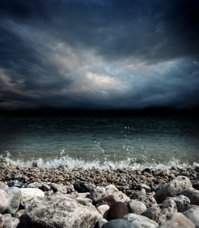 stormy sea: sea coast, stones, waves and dark dramatic stormy sky landscape