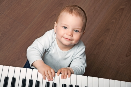 portrait of little baby child  play music on black and white piano keyboard photo