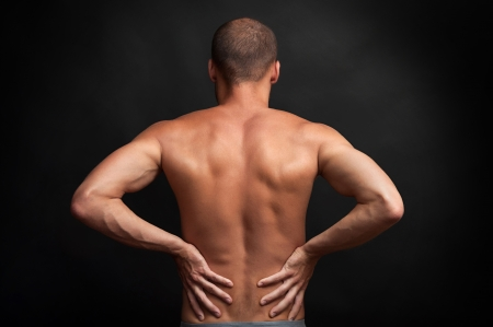strong muscular man holding his back with hands - spine ache concept Stock Photo - 23219035