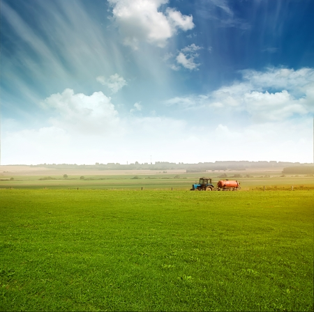 agriculture machinery: tractor in green field over blue cloudy sky gather crops in summer or autumn