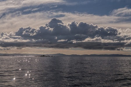 peruvian ethnicity: A huge cloud over Lake Titicaca view of the border with Bolivia. Stock Photo