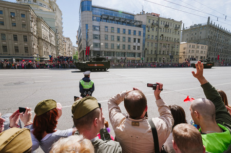 common people: MOSCOW-MAY 9, 2015: Victory parade dedicated to the 70th anniversary of the Soviet victory over Germany. People on the streets of Moscow greeted Pass technique. Organization of view of the parade for the common people.