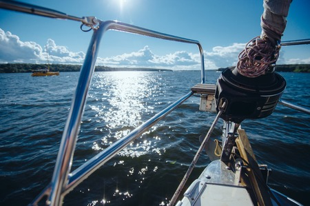 sailing ships: View from the board of a sailing yacht on the waters, sailing ships and the forest growing along the coast, as well as peoples homes. Stock Photo