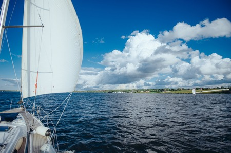 sail board: View from the board of a sailing yacht on the waters, sailing ships and the forest growing along the coast, as well as peoples homes. The yacht is going full speed under sail.