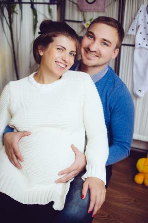 Familia fotografiar para parejas enamoradas. estudio fotográfico en casa. El hombre y la mujer embarazada que abrazan la mentira en el suelo.