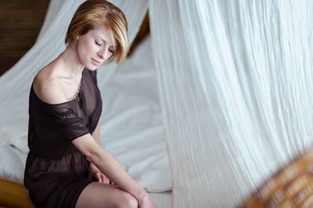 head bowed: blond head bowed sits on a snow-white bed Stock Photo