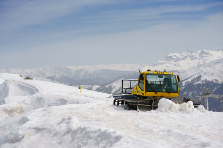 snow grooming machine: snowcat on ski slope on a background of mountain peaks