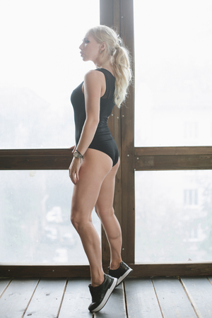 tiptoes: sports girl in a black body at the window standing on tiptoes