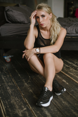 woman with bare feet in black sneakers and body sits near a large bed on the wooden floor, looking at the camera and posing for a photograph with his hands near the face. Stock Photo