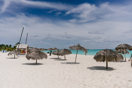 cana: Beach umbrellas made of palm branches on the shores of the Caribbean Sea on the white sand beach of Cayo Largo, Cuba