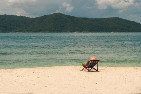 Koh He A girl in a hat is resting on the beach sitting in a deckchair. Stock Photo