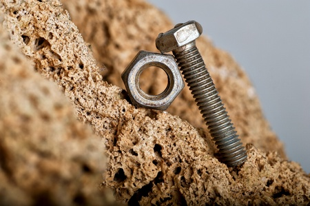 Metal bolt pushing a nut on mountain Stock Photo