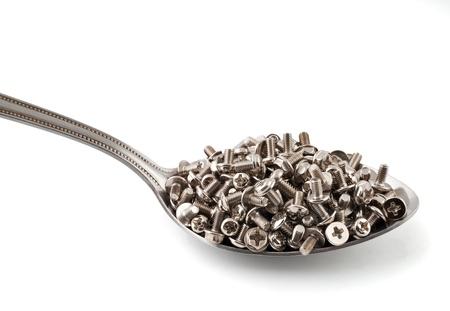 Metal spoon full of brilliant metal screws Stock Photo