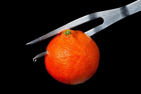 tangerine on a plug on a black background