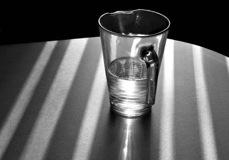 The jug shined with the sun with water on a table Stock Photo