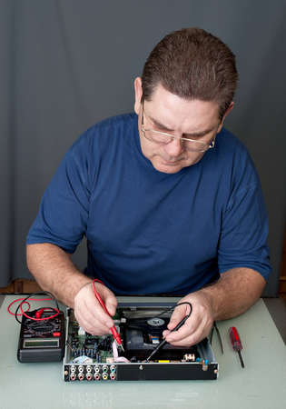 The man with a screw-driver and a tweezers repairing DVD a player