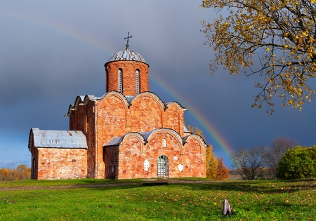 Russian ancient brick church against a rainbow Stock Photo