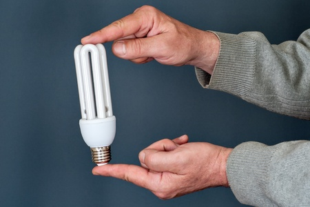 man s hands holding an energy saving bulb photo