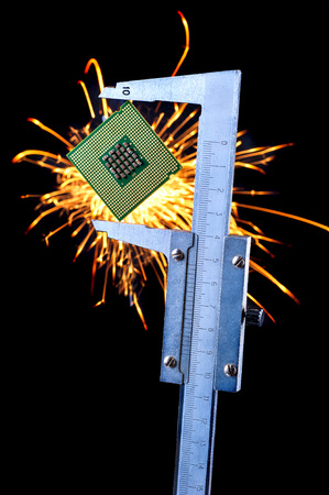 the microprocessor clamped in a caliper with sparks on a background photo