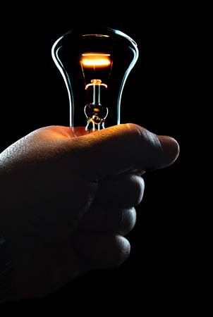 hand with a shining electric bulb on a black background Stock Photo