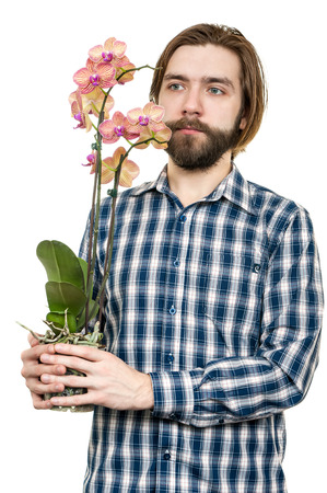the young man with a beard, holds an orchid flower in hand, is isolated on a white background