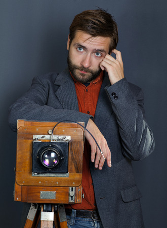 the young man with a beard taking photos with vintage camera Stock Photo