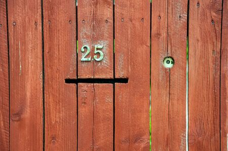 painted wooden fence made of planks with a number and a slot for mail