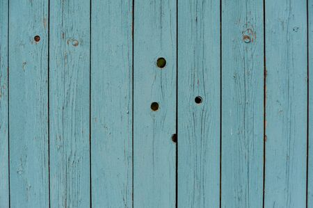 Texture of vertical wooden planks with peeling turquoise blue color paint. Detailed background photo texture.