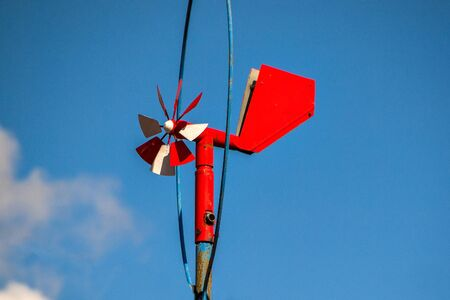 homemade red weather vane with a propeller against a blue sky .