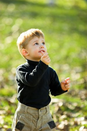 A little boy eating short stick in the park Stock Photo