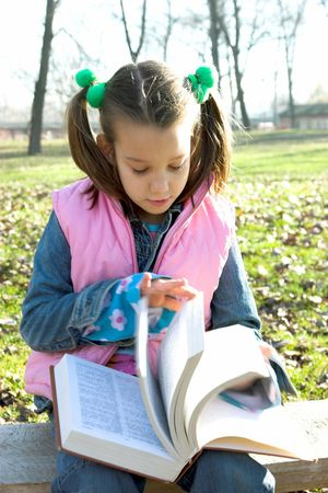 little pretty child reading the book in the park photo