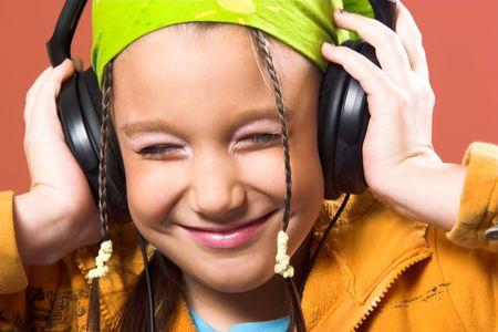little pretty child listening music in headphones