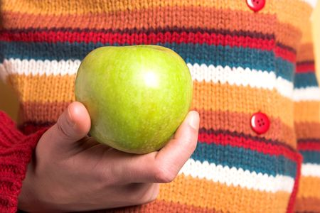 details colorful sweater and green apple in closeup  photo